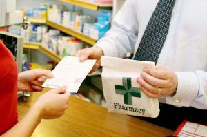 Woman's hand receiving receipt and drugs from pharmacist